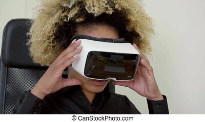 Young woman wearing virtual reality glasses gripping them...