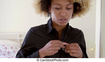 Sleepy black woman buttons her blouse by the bed as she...