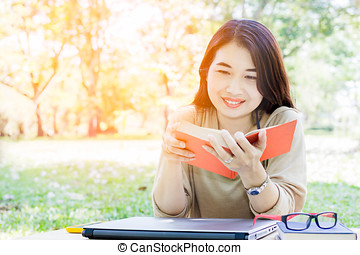 Asian young lady read book at outdoor in park