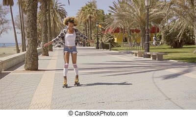 Woman Riding On Vintage Roller Skates - Young woman dressed...