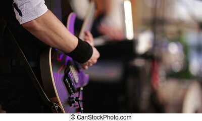 Guitarist playing an electric guitar - musical band performs...