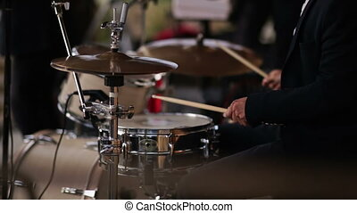 drummer playing an acoustic drum set - musical band performs...