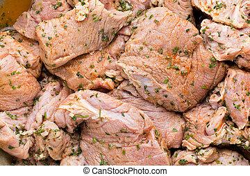 Fresh pork meat pieces in marinade.