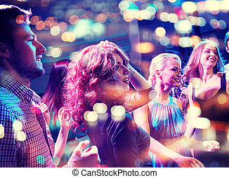 smiling friends dancing in club - party, holidays,...
