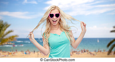 happy young blonde woman or teenager in sunglasses -...