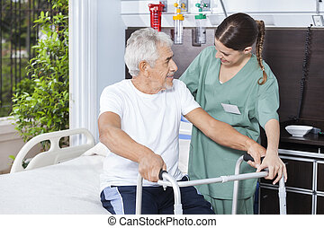 Smiling Man Being Helped By Nurse In Using Zimmer Frame -...