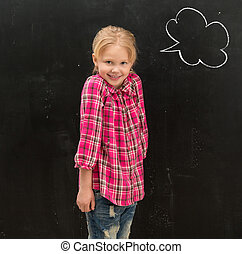 cute little schoolgirl standing in front of the blackboard with drawn cloud