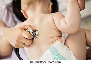 Pediatrician's Hand Examining Baby Though Stethoscope -...