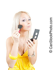 woman putting make up on her face - A young woman putting...