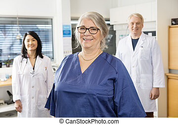 Senior Nurse Smiling While Colleagues Standing In Background...