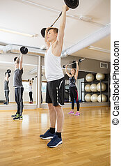 Man And Woman Exercising With Barbells In Gym - Full length...