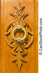 Brass door knocker on a wooden carving - Old brass door...