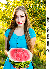 Smiling young attractive girl holding half of watermelon -...
