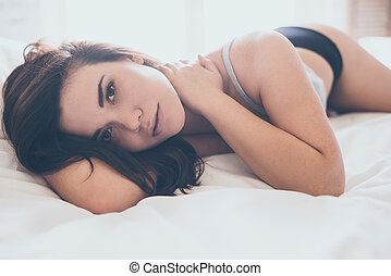 Lets stay in bed a little longer. Beautiful young woman in...
