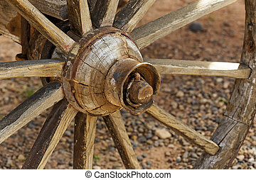 wooden wagon wheel in a western farm - detail of a rustic...
