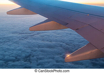 Wing of airplane above clouds