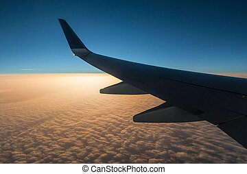 Wing of airplane above clouds at sunset