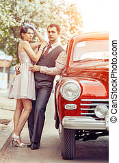 Pretty couple is going to make a jorney on their red car.
