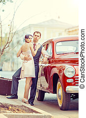 Pretty couple is going to make a jorney on their red car...