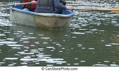 Boat with Paddles Approaching - A boat with passengers with...