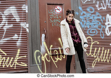 young pretty stylish teenage girl outside in city wall with graffiti smoking cigarette at forbidden smoke sign