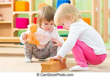 Pensive kids playing in kindergarten room