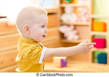 Happy kid playing in kindergarten room