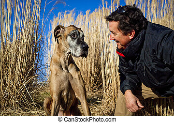 Handsome man facing his dog