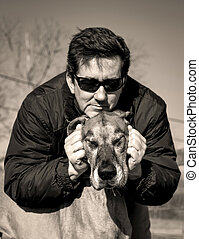Handsome man leaning over his dog