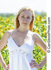 Portrait of a beautiful young blonde woman in a white dress...