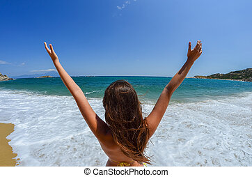 Say hello to the beach - Young girl with her hands up,...