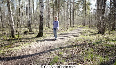 The happy woman goes on a footpath in park in  early spring