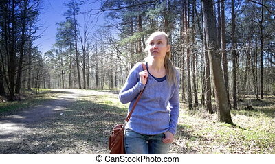 The happy woman goes on a footpath in park in early spring -...