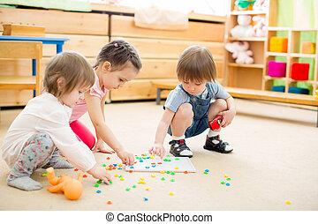 kids playing mosaic game in kindergarten room