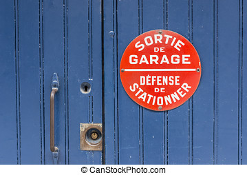 Blue wooden door with No parking sing in french.