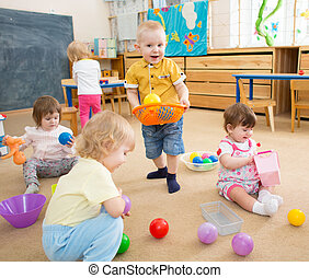 kids playing with balls in kindergarten room - Group of kids...