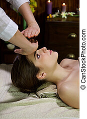 Beautiful serious calm peaceful woman getting reiki with hands in front of head