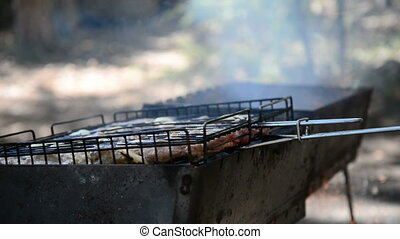 Meat grilling on with burning wood. Cook fanning fire....