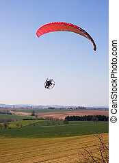 A powered paraglider pilot in flight over the landscape