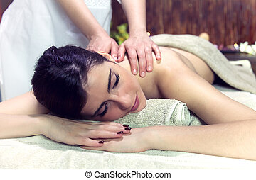 Woman getting massage in relaxing spa dreaming