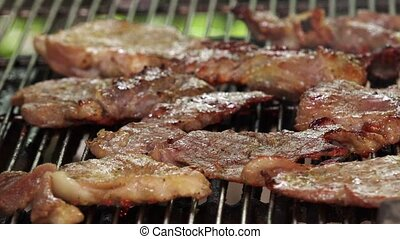 Grilling pork chops on barbecue, tiny juicy meat slices...