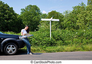 Woman reading a map by the roadside with blank signpost.