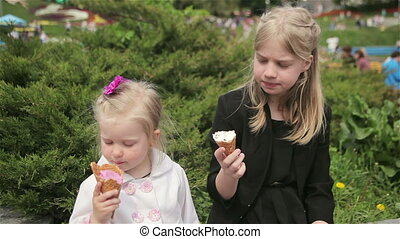 Pretty sisters eating ice cream in the summer the Park