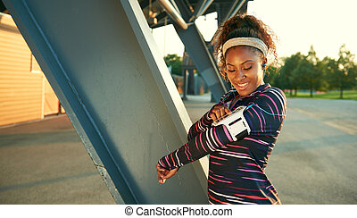 African american fit woman choosing music from an app for...