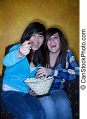 Pretty Hispanic girls with popcorn watching television