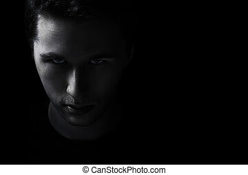 dark young adult man portrait fade in black background