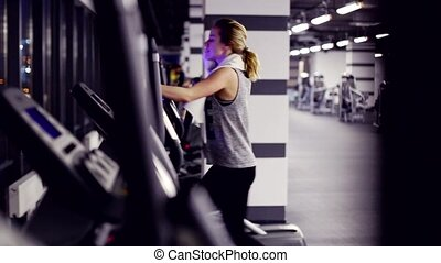 view of emty gym with one girl on elliptical trainer