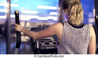 Workout on elliptical trainer in the evening gym