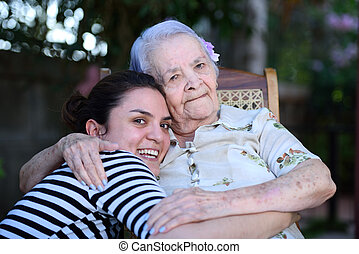 Grandma and grandaughter together hugging and laughing