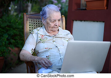 Grandma using a laptop - Smart grandma using and working on...